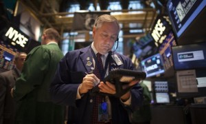 A trader works on the floor of the New York Stock Exchange during the opening bell in New York, November 27, 2013. Credit: Reuters/Carlo Allegri