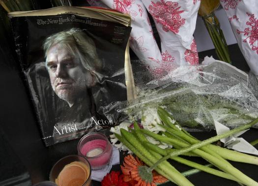 A copy of a New York Times Magazine with a photo of movie actor Philip Seymour Hoffman on the cover is pictured as part of a makeshift memorial in front of his apartment building in New York February 3, 2014. Credit: Reuters/Carlo Allegri