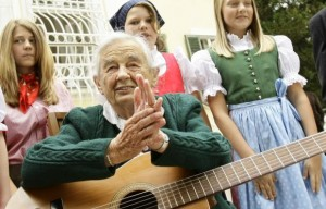 Maria von Trapp, daughter of Austrian Baron Georg von Trapp, prepares to play a guitar and sing with traditionally dressed children in front of her former home, Villa Trapp, in Salzburg in this July 24, 2008 file photo. Credit: Reuters/Leonhard Foeger/Files