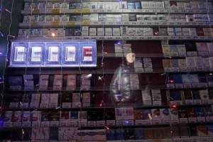 A woman is reflected in a window displaying packs of cigarettes on a street in Russia's Siberian city of Krasnoyarsk January 24, 2013. Credit: Reuters/Ilya Naymushin