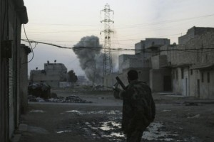 Smoke rises while a Free Syrian Army fighter stands at the Karm al-Tarab neighborhood frontline in Aleppo February 1, 2014. CREDIT: REUTERS/AMMAR ABDULLAH