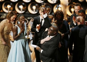 Director and producer Steve McQueen (R) celebrates after accepting the Oscar for best picture with Lupita Nyong'o (L) at the 86th Academy Awards in Hollywood, California March 2, 2014.  Credit REUTERS/Lucy Nicholson