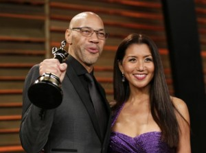 "Writer John Ridley holds up his award for best adapted screenplay for ""12 Years a Slave"" as he arrives with his wife Gayle at the 2014 Vanity Fair Oscars Party in West Hollywood"