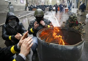 Pro-Russian men gather around a fire at a barricade near the police headquarters in Slaviansk April 13, 2014. One pro-Russian activist was killed in the east Ukrainian city of Slaviansk in clashes with forces loyal to the government in Kiev, Russian news agency RIA reported on Sunday, citing a local militant. REUTERS/Gleb Garanich