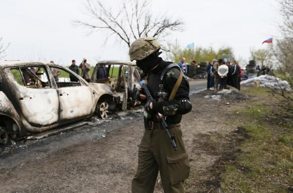 A Pro-Russian militant walks near a checkpoint that was the scene of a gunfight overnight near the city of Slaviansk, April 20, 2014. CREDIT: REUTERS/GLEB GARANICH