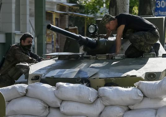 An armored personnel carrier is seen near a barricade around the state security service building in Slaviansk, April 26, 2014. CREDIT: REUTERS/GLEB GARANICH