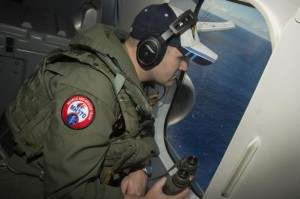 Naval Aircrewman 2nd Class Karl Shinn looks out a window of a P-8A Poseidon while flying over the Indian Ocean during a search mission to locate Malaysia Airlines flight MH370, in this U.S. Navy handout photo taken April 10, 2014.  REUTERS/U.S. Navy/Chief Mass Communication Specialist Keith DeVinney/Handout via Reuters