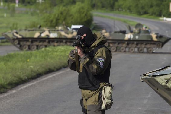 A Ukrainian soldier, with armoured personnel carriers behind him, points his weapon at an approaching car at a checkpoint near the town of Slaviansk in eastern Ukraine Credit: Reuters/Baz Ratner
