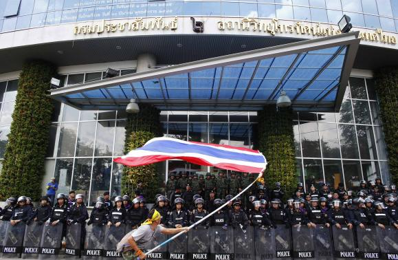 An anti-government protester waves a national flag in front of riot police officers and soldiers guarding the entrance of the National Broadcast Services of Thailand (NBT) television station in Bangkok May 9, 2014. CREDIT: REUTERS/ATHIT PERAWONGMETHA