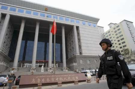 A special force policeman patrols in front of the Intermediate People's Court in Urumqi, Xinjiang Uigur Autonomous Region, October 12, 2009. A Chinese court in the restive far western region of Xinjiang on Monday sentenced six people to death for murder and other crimes committed during ethnic rioting in July in which almost 200 people were killed. Picture taken October 12, 2009. REUTERS/China Daily
