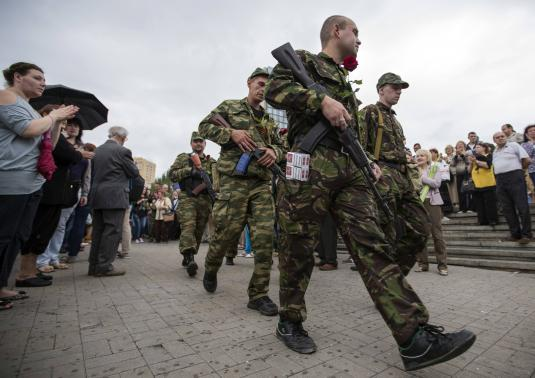 Armed pro-Russian separatists of the self-proclaimed Donetsk People's Republic walk after an oath taking ceremony in the city of Donetsk June 21, 2014. CREDIT: REUTERS/SHAMIL ZHUMATOV