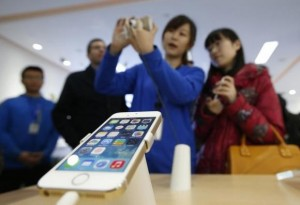 A staff of a China Mobile shop explains a function of the iPhone 5s to a customer in Beijing January 17, 2014. Credit: Reuters/Kim Kyung-Hoon