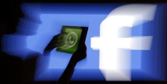 A woman holds a tablet displaying WhatsApp's logo in front of the screen with the Facebook logo in this photo illustration taken in Prague February 20, 2014. Credit: Reuters/David W Cerny