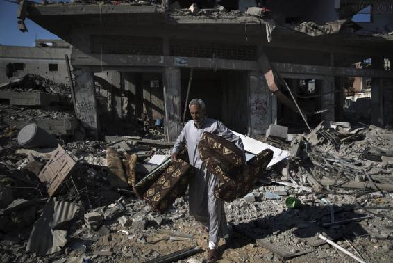 A Palestinian man salvages belongings from damaged buildings in the Shejaia neighbourhood, which witnesses said was heavily hit by Israeli shelling and air strikes during an Israeli offensive, in Gaza City July 27, 2014. Credit: Reuters/Finbarr O'Reilly