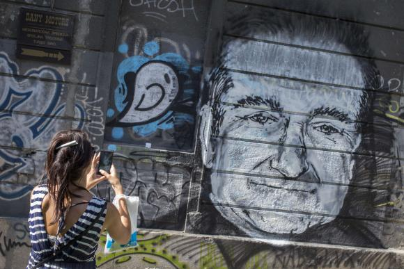A woman takes a picture of a mural depicting late actor Robin Williams in Belgrade