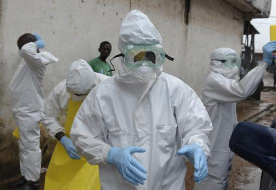 Health workers wearing protective clothing prepare to carry an abandoned dead body presenting with Ebola symptoms at Duwala market in Monrovia August 17, 2014. CREDIT: REUTERS/2TANGO