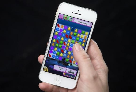 A woman poses for a photo illustration with an iPhone as she plays Candy Crush in New York February 18, 2014. Credit: Reuters/Carlo Allegri