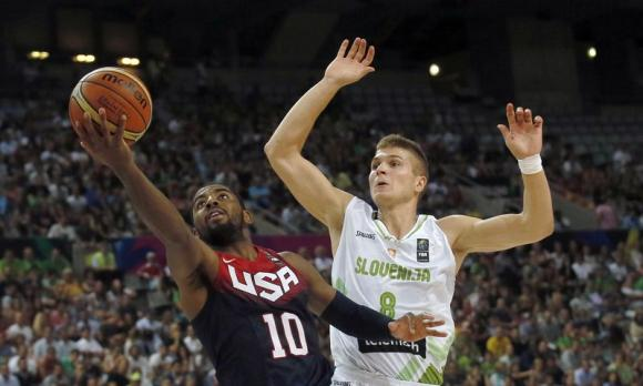 Kyrie Irving of the U.S. (L) goes up for a basket past Slovenia's Edo Muric during their Basketball World Cup quarter-final game in Barcelona September 9, 2014. CREDIT: REUTERS/ALBERT GEA