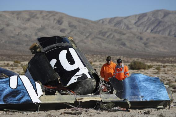 Sheriffs' deputies look at wreckage from the crash of Virgin Galactic's SpaceShipTwo near Cantil, California November 2, 2014. CREDIT: REUTERS/DAVID MCNEW