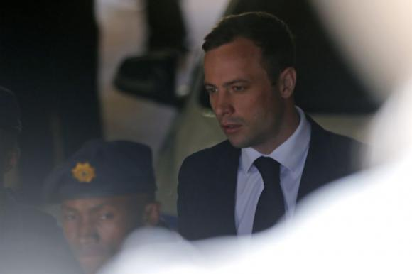 South African Olympic and Paralympic sprinter Oscar Pistorius is led to a prison van after his sentencing in Pretoria October 21, 2014. CREDIT: REUTERS/MIKE HUTCHINGS