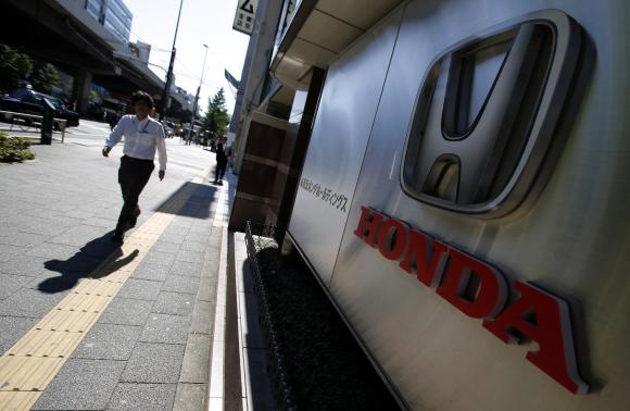 A pedestrian walks past a logo of Honda Motor Co outside the company's dealership in Tokyo October 28, 2014. CREDIT: REUTERS/YUYA SHINO