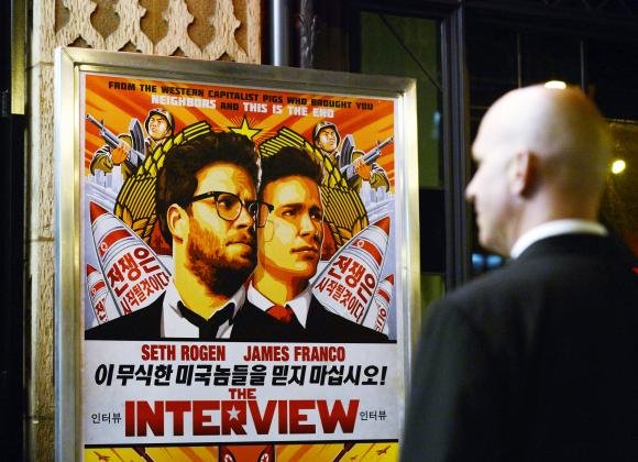 A security guard stands at the entrance of United Artists theater during the premiere of the film ''The Interview'' in Los Angeles, California December 11, 2014. CREDIT: REUTERS/KEVORK DJANSEZIAN