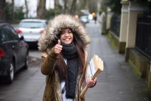 """Ready to distribute copies of the Pasugo (God's Message) magazine in cold weather, an Iglesia Ni Cristo member -- all geared up for the cold -- makes a """"thumbs up"""" sign as she carries envelopes containing Pasugo magazines in Bonn, Germany. (Eagle News Service)"""