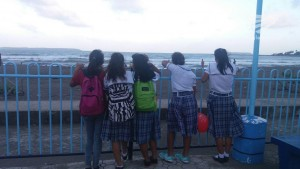 School kids watching the waves along Baybay boulevard in Borongan City.
