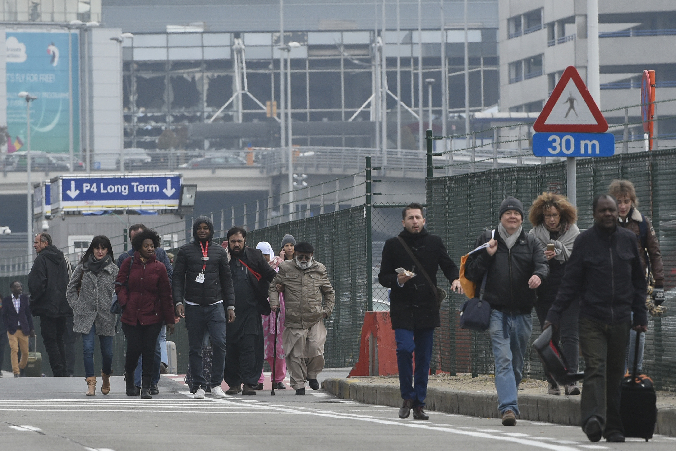 Passengers leave Brussels airport, on March 22, 2016 in Zaventem , following its evacuation after at least 13 people were killed and 35 injured as twin blasts rocked the main terminal of Brussels airport.AFP PHOTO / JOHN THYS / AFP / JOHN THYS
