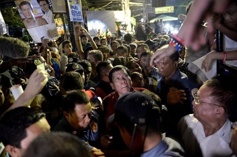 Davao City mayor and presidential candidate Rodrigo Duterte (C) is greeted by his supporters as he leaves after his party's proclamation rally in Manila on February 9, 2016. A cliffhanger race to lead the Philippines began February 9 with the adopted daughter of a dead movie star and a tough-talking politician who claims to kill criminals among the top contenders. AFP PHOTO / NOEL CELIS / AFP / NOEL CELIS