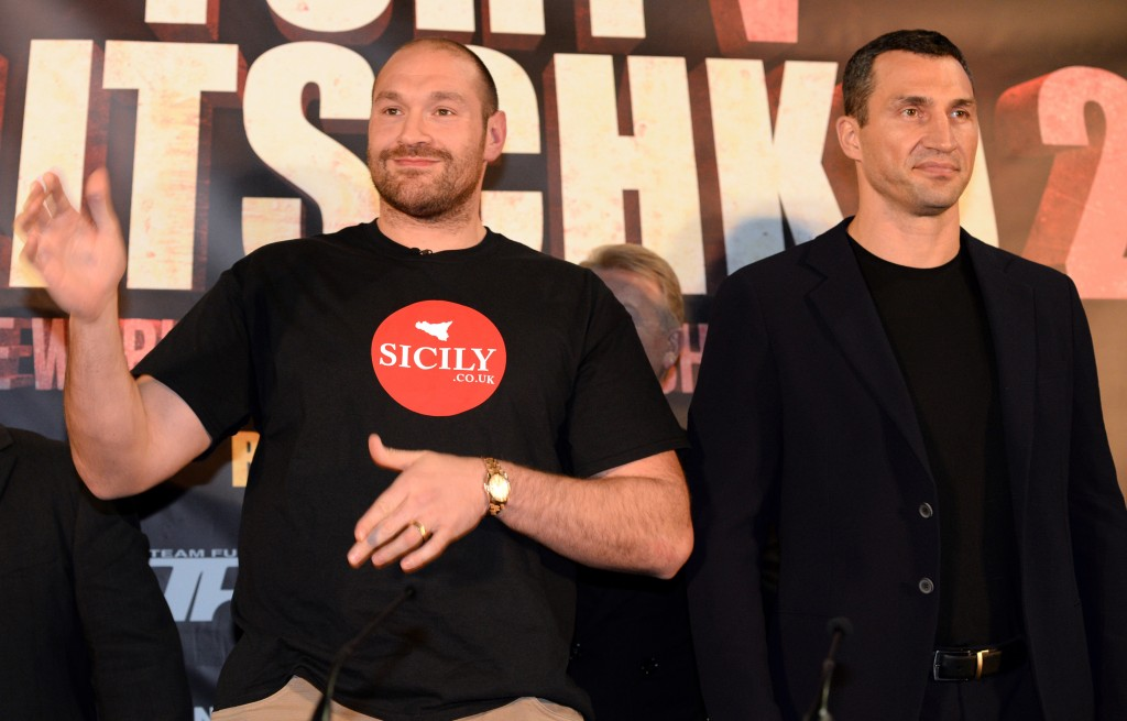 "British heavyweight boxer Tyson Fury (L) poses alongside Ukrainian heavyweight Wladimir Klitschko, during a press conference to publicise their forthcoming world heavyweight title fight, at the Manchester Arena in Manchester, north-west England on April 27, 2016. Wladimir Klitschko has insisted he was ""glad"" to have lost his world heavyweight titles to Tyson Fury in December 2015, ahead of a re-match with the British boxer on July 9, 2016. With Klitschko's loss to Fury, the belts are now spread far and wide, with Fury holding the WBA and WBO titles, fellow Briton Anthony Joshua the IBF champion, and Deontay Wilder of the United States, the World Boxing Council's heavyweight title. / AFP PHOTO / OLI SCARFF"