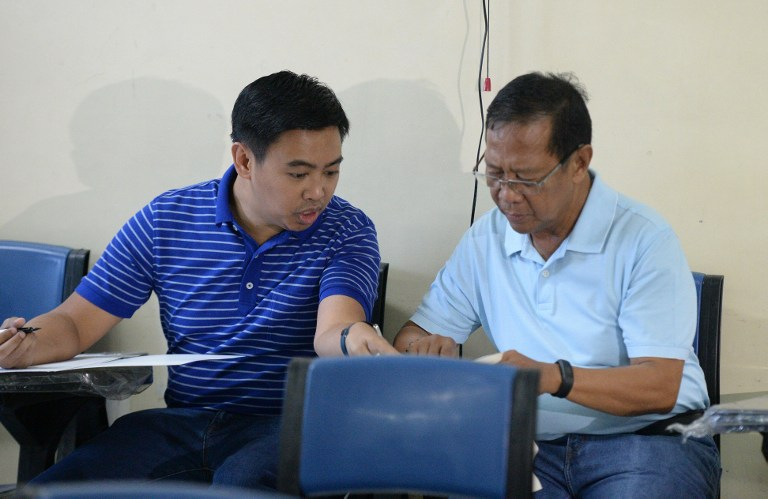 Philippines' Vice President and a presidential candidate Jejomar Binay (R) along with his son former mayor Junjun Binay cast their votes at a polling station in the financial district of Manila on May 9, 2016.  Voting was underway in the Philippines on May 9 to elect a new president, with anti-establishment firebrand Rodrigo Duterte the shock favourite after an incendiary campaign in which he vowed to butcher criminals. / AFP PHOTO / TED ALJIBE