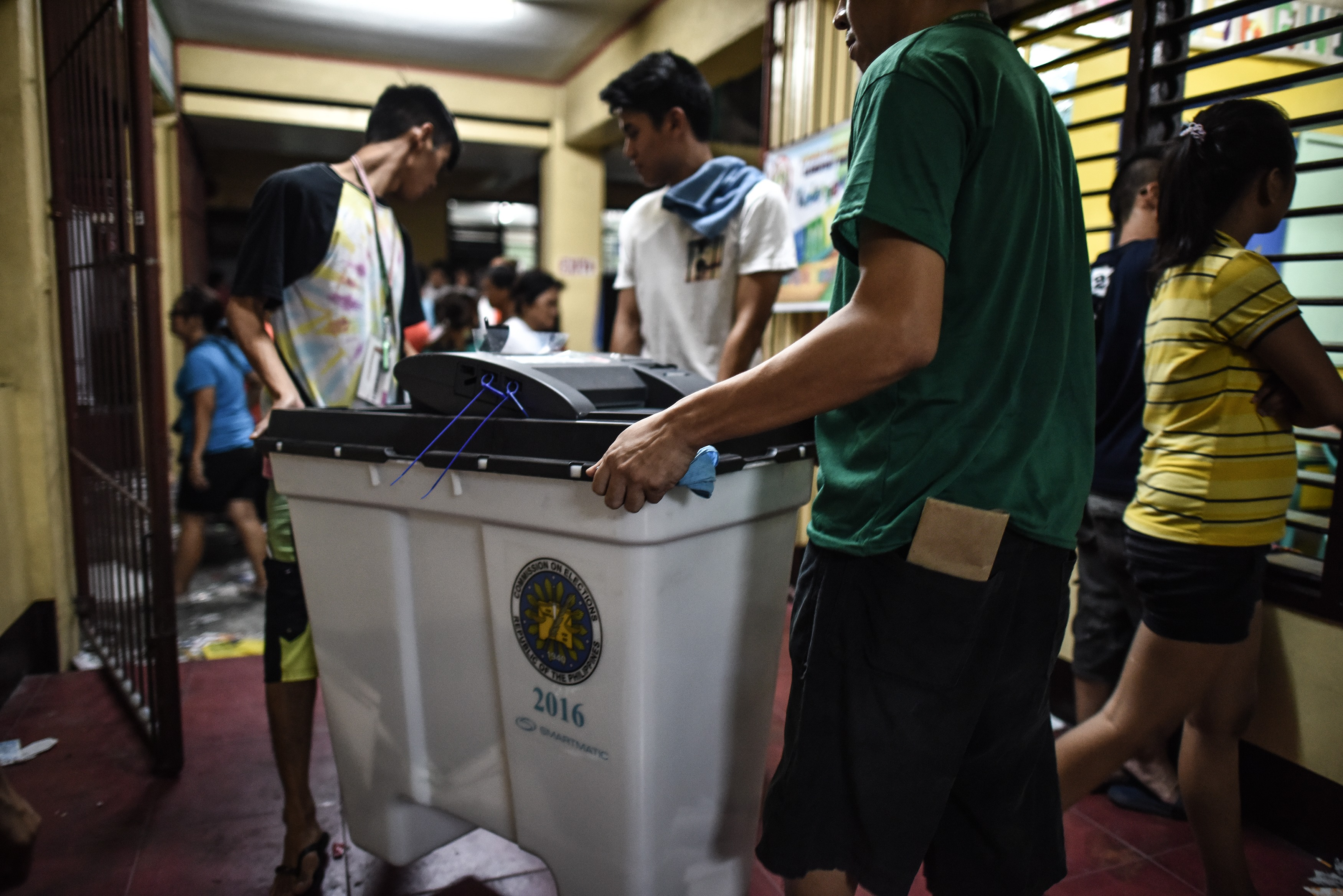 Polling officers carry a vote counting machine after polls closed in the presidential election in Manila on May 9, 2016./ AFP PHOTO / MOHD RASFAN
