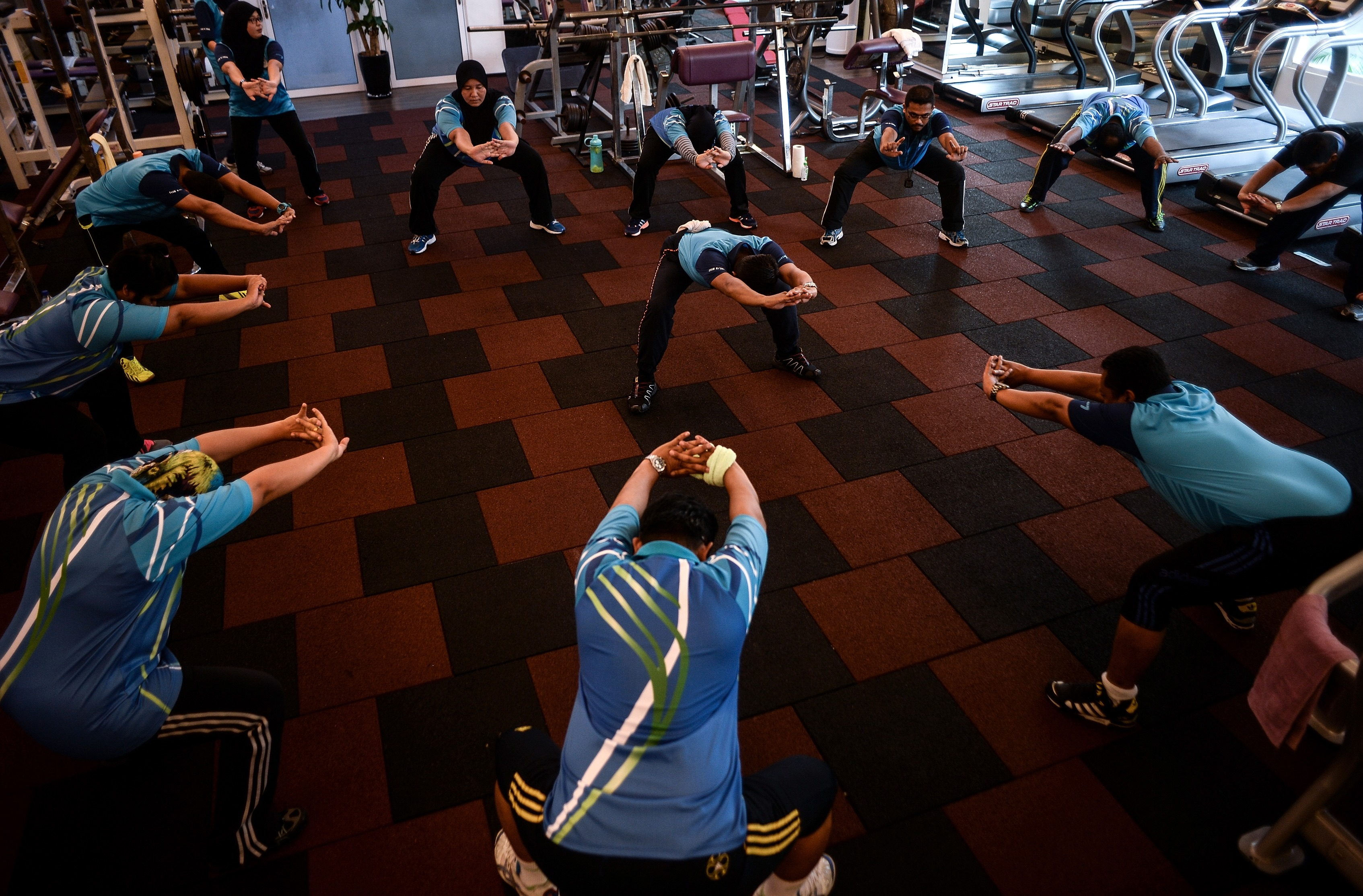 "This picture taken on January 21, 2016 shows Malaysian police personnel stretching as they take part in the special weight-loss and fitness programme ""Trim and Fit"" at police headquarters in Kuala Lumpur. The group is among thousands of Malaysian officers who have been ordered to slim down amid concern that fast-expanding waistlines could limit their crime-fighting abilities.    AFP PHOTO / MANAN VATSYAYANA / AFP PHOTO / MANAN VATSYAYANA"