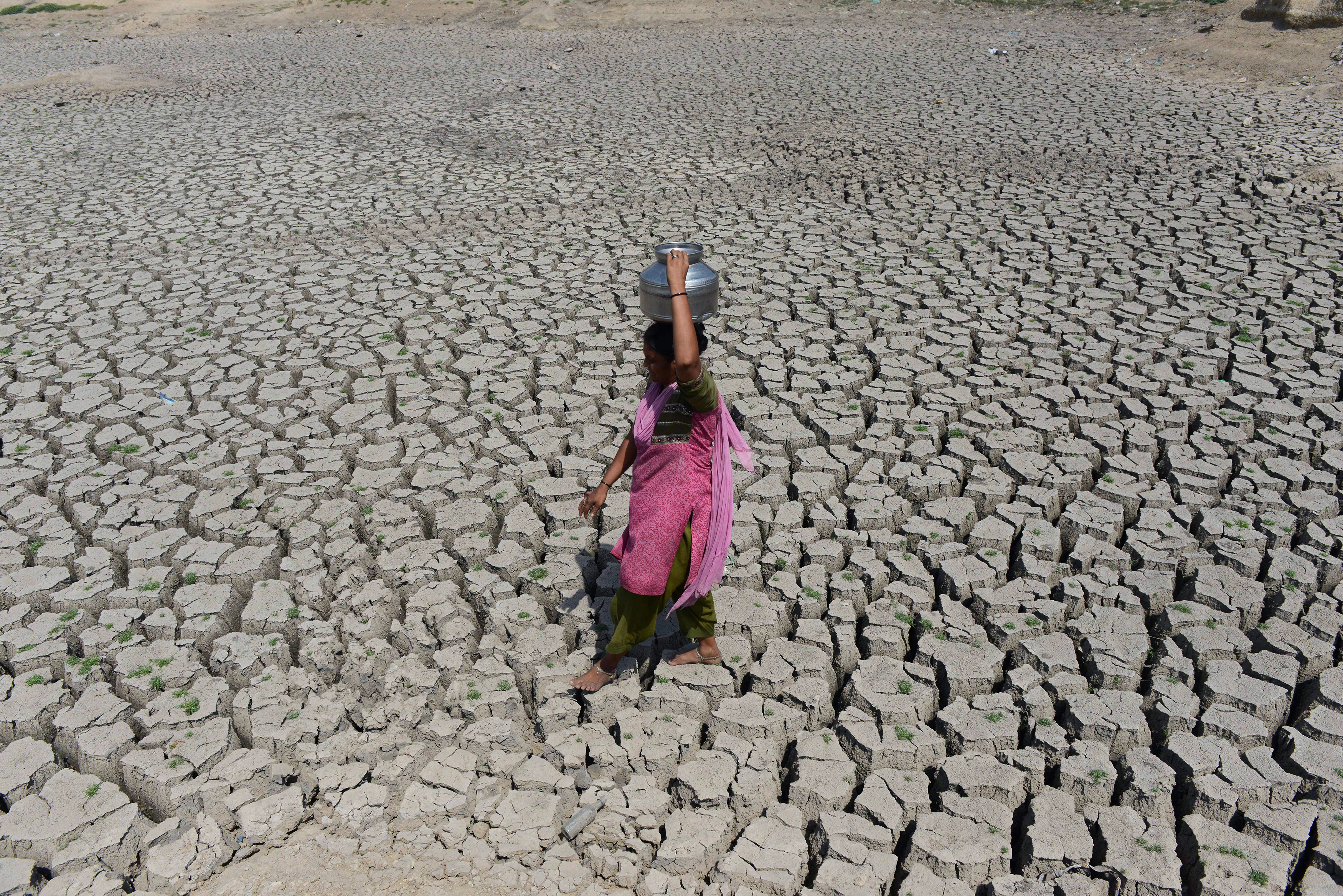 An Indian woman walks on the parched bed of Chandola Lake with a metal pot on her head to fetch water in Ahmedabad on May 20, 2016. India is facing its worst water crisis in decades, with about 330 million people, or a quarter of the population, suffering from drought after two weak monsoons. / AFP PHOTO / SAM PANTHAKY