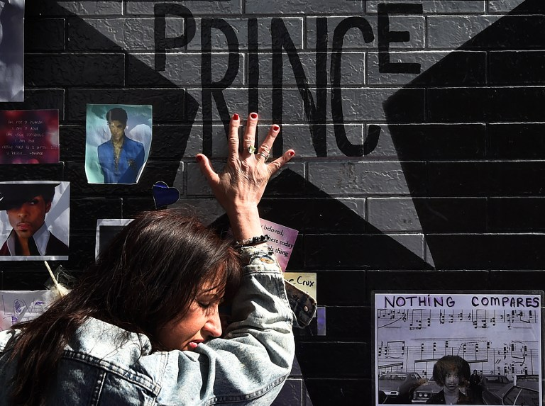 (FILES) This file photo taken on April 23, 2016 shows  Prince fan Ann Sawatzky touching the star of music legend Prince who died suddenly at the age of 57, at the First Avenue club where he started his music career in Minneapolis, Minnesota, on April 23, 2016. Prince died from an overdose of painkillers, a report said on June 2, 2016, quoting the ongoing investigation. The Star Tribune newspaper in Prince's hometown Minneapolis quoted an anonymous source as saying that the singer had overdosed on opioid pain medication. Officials declined comment.  / AFP PHOTO / Mark Ralston