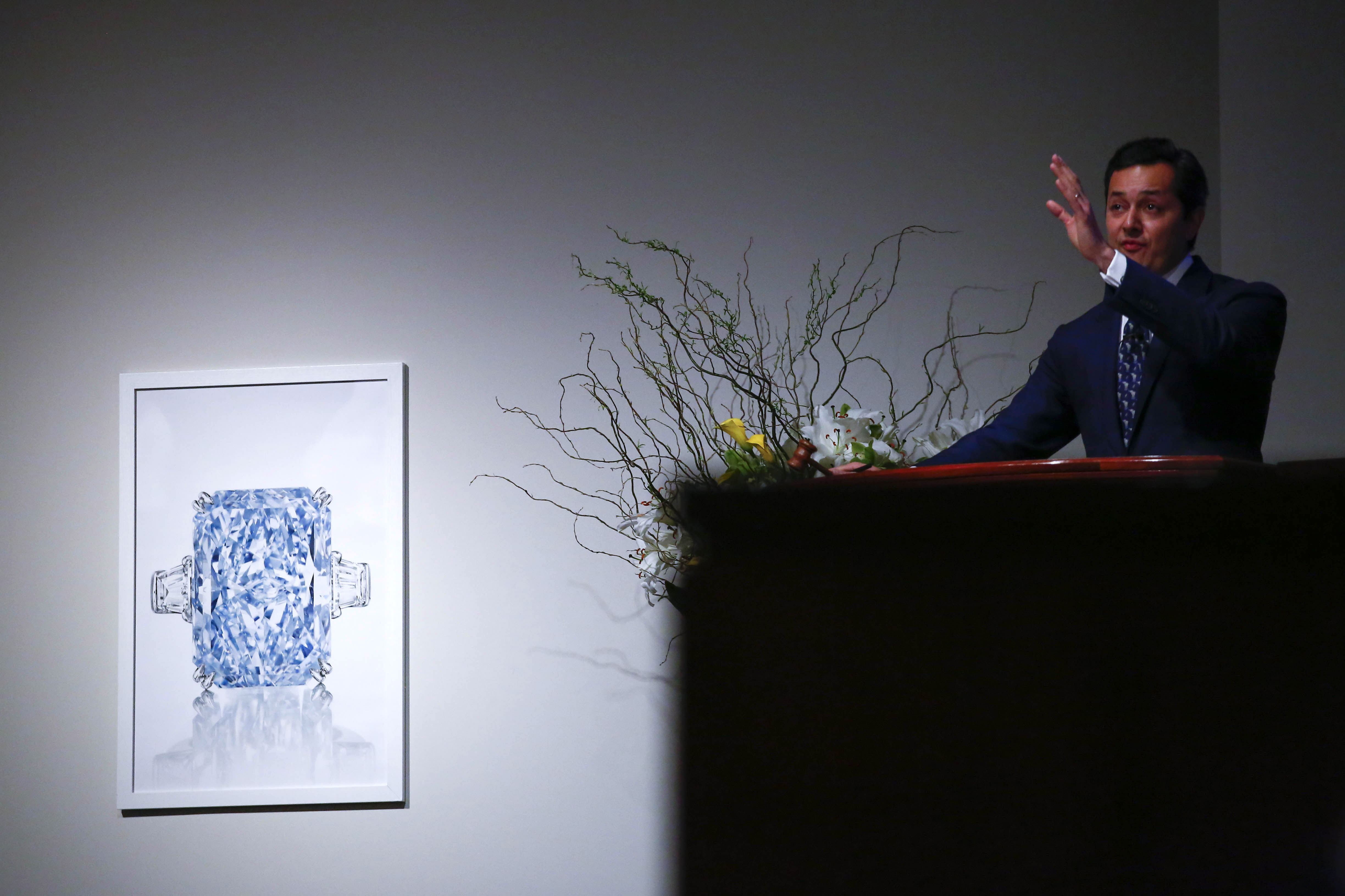 Rahul Kadakia, Christie's International Head of Jewelry takes bids during the auction Magnificent Jewels and The Cullinan Dream (L) at Christie's in New York, June 9, 2016. The Cullinan Dream is the largest Fancy Intense Blue diamond at auction, weighing 24.18 carats. / AFP PHOTO / KENA BETANCUR / RESTRICTED TO EDITORIAL USE - MANDATORY MENTION OF THE ARTIST UPON PUBLICATION - TO ILLUSTRATE THE EVENT AS SPECIFIED IN THE CAPTION