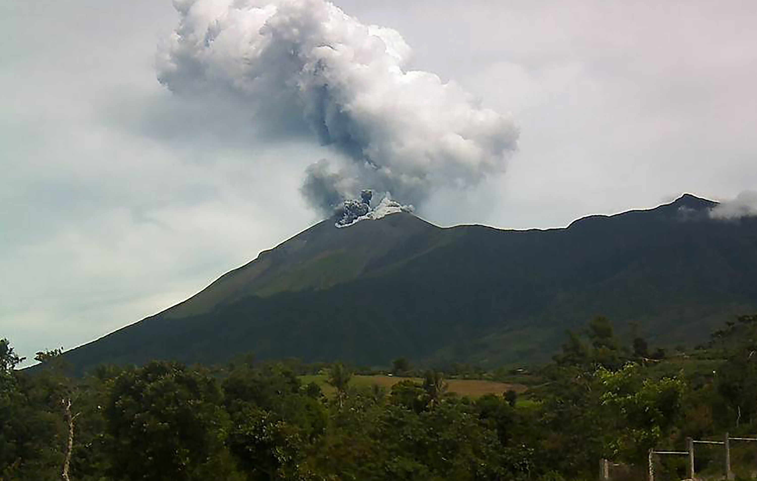 "This handout photo taken on June 18, 2016 and released by Philippines Institute of Volcanology and Seismology (PHIVOLCS) shows Kanlaon volcano as it spewed ash into the air as seen from the observation post of the PHIVOLCS in La Carlota town, Negros Occidental province, central Philippines. Mount Kanlaon, located in the central island of Negros, launched a plume of whitish-grey ash about 1.5 kilometres (almost a mile) into the air, said Kenn John Veracruz of the official Philippine Institute of Volcanology and Seismology. / AFP PHOTO / PHILIPPINES INSTITUTE OF VOLCANO / RESTRICTED TO EDITORIAL USE - MANDATORY CREDIT ""AFP PHOTO / PHILIPPINES INSTITUTE OF VOLCANOLOGY AND SEIMOLOGY"" - NO MARKETING NO ADVERTISING CAMPAIGNS - DISTRIBUTED AS A SERVICE TO CLIENTS"