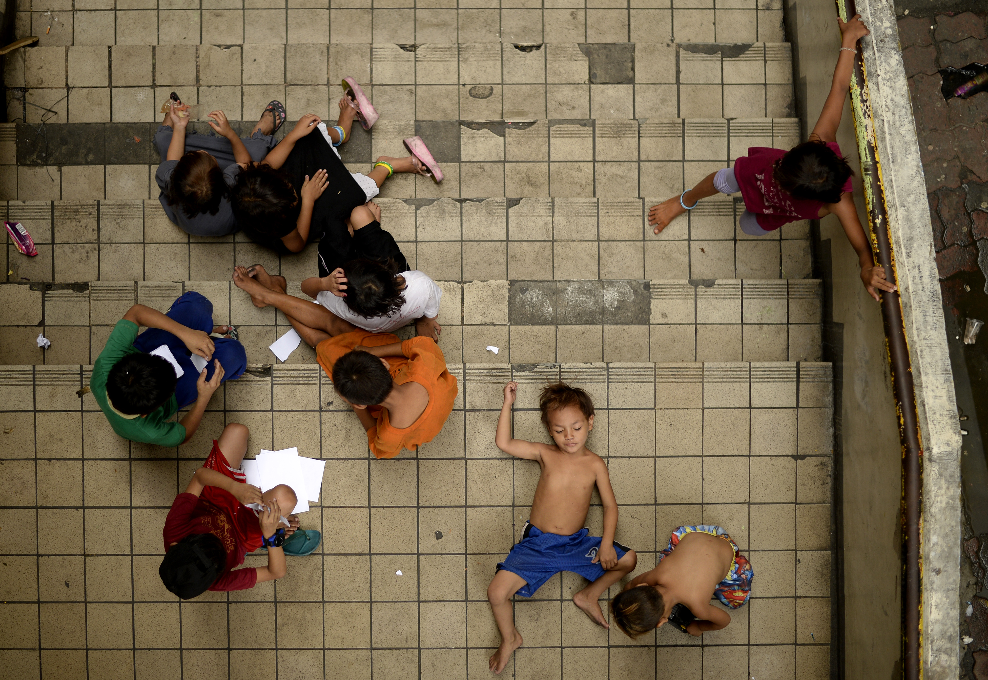 "(File photo) Homeless children play on a staircase at the Light Railway Train (LRT) Carriedo station in Manila on May 26, 2016. The Aquino government claims that 1.4 million Filipino families were able to escape from the ""poverty threshold"" because of its Pantawid Pamilyang Pilipino Program (4Ps) / AFP PHOTO / NOEL CELIS"