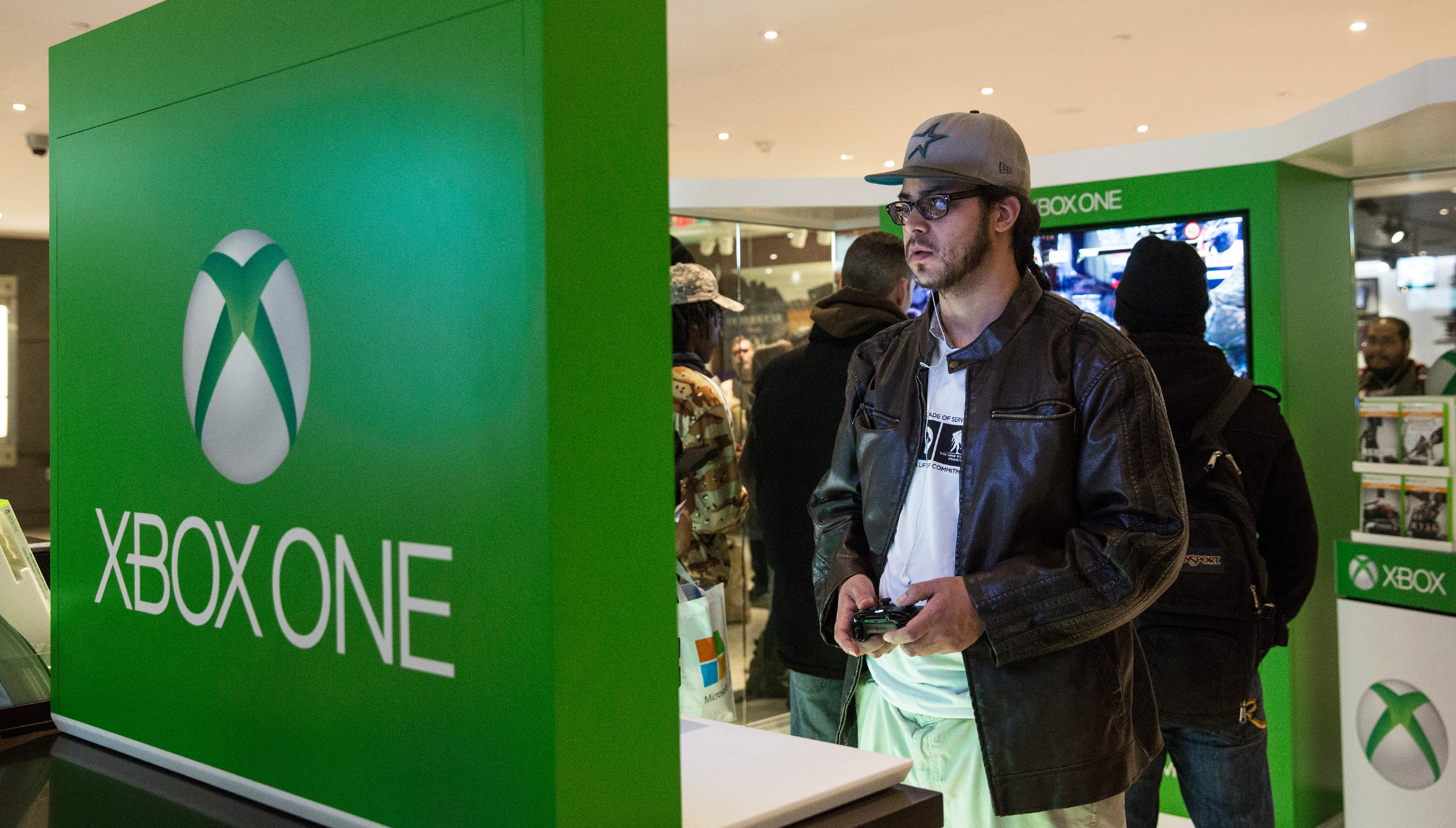 """NEW YORK, NY - NOVEMBER 22: A man plays an XBox One - a new video game console and home entertainment system made by Microsoft- while waiting in line to buy an XBox One from a Microsoft """"pop-up shop"""" at the Time Warner Center at Columbus Circle on 22, 2013 in New York City. The X Box One arrives just in time for the holiday season, and will be competing against the Sony Playstation Four, which came out last week.   Andrew Burton/Getty Images/AFP"""