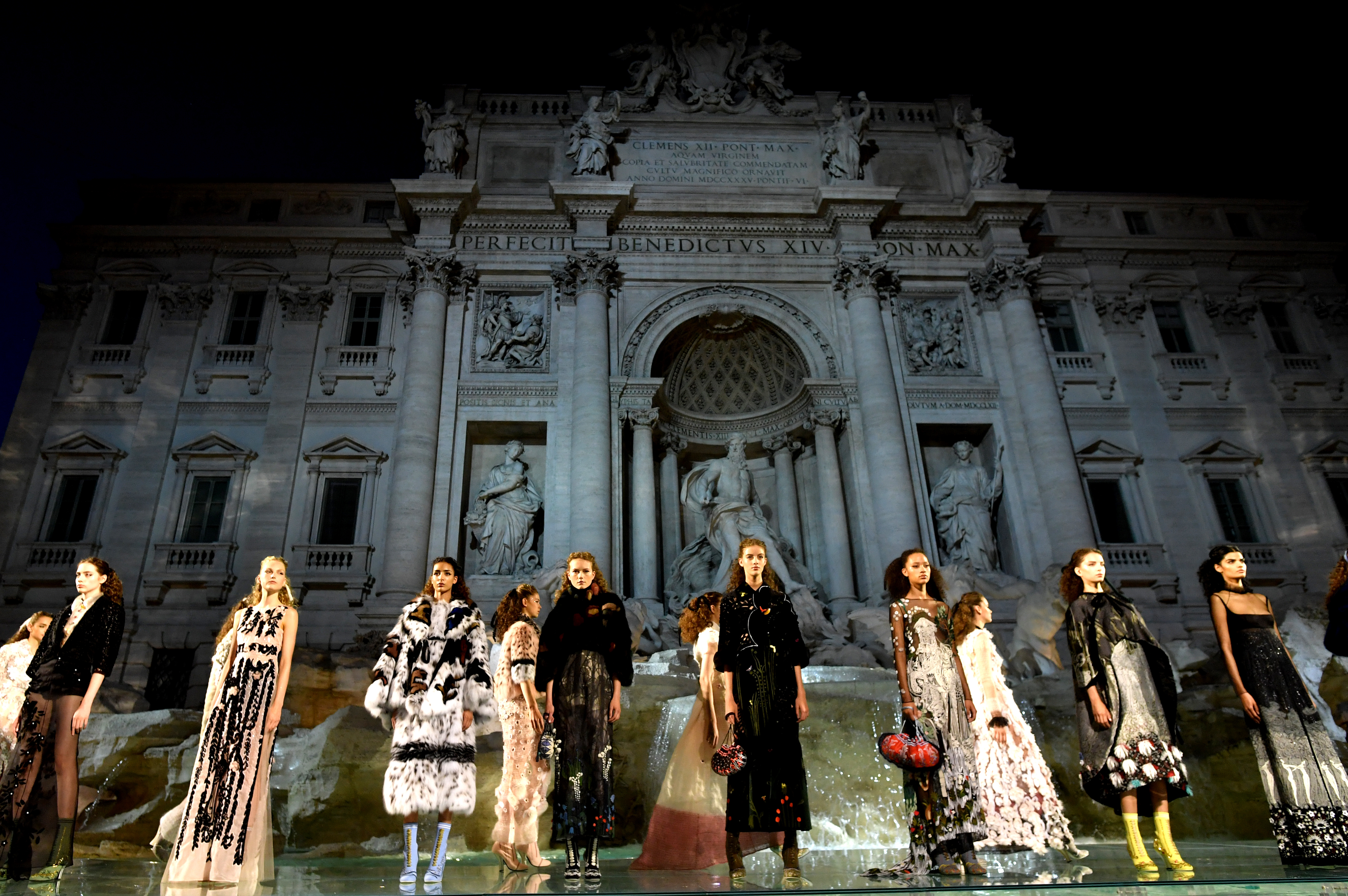 Models present creations by Fendi during a fashion show at the Trevi Fountain in Rome on July 7, 2016 to celebrate the 90th anniversary of the fashion house. / AFP PHOTO / TIZIANA FABI
