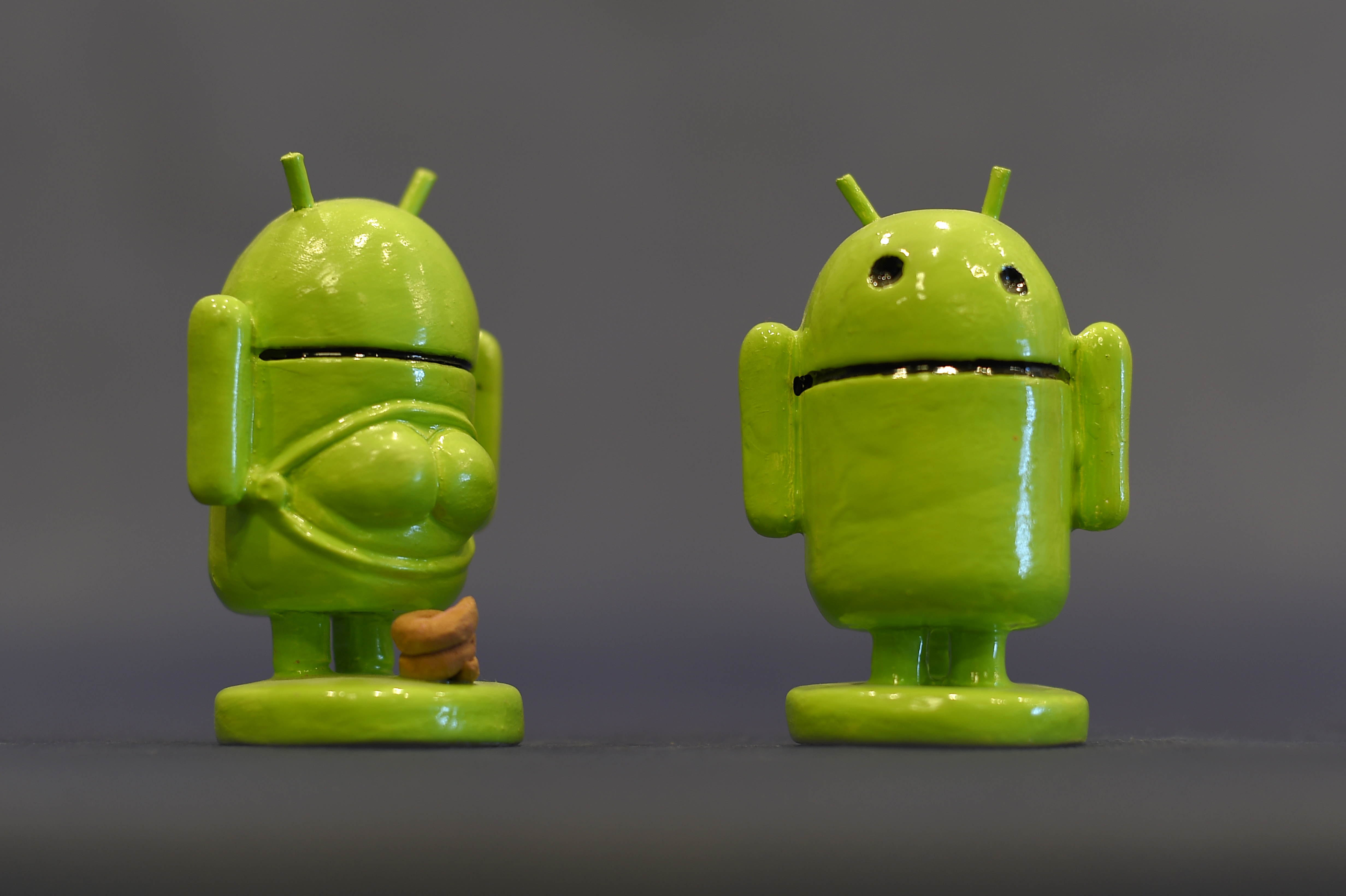 """A picture taken on November 19, 2015 shows ceramic figurines representing Android logo, called """"Caganers"""" during their presentation in Torroella de Montgri, near Gerona. Statuettes of well-known people defecating are a strong Christmas tradition in Catalonia, dating back to the 18th century as Catalans hide caganers in Christmas Nativity scenes and invite friends to find them. The figures symbolize fertilization, hope and prosperity for the coming year. AFP PHOTO / LLUIS GENE / AFP PHOTO / LLUIS GENE"""