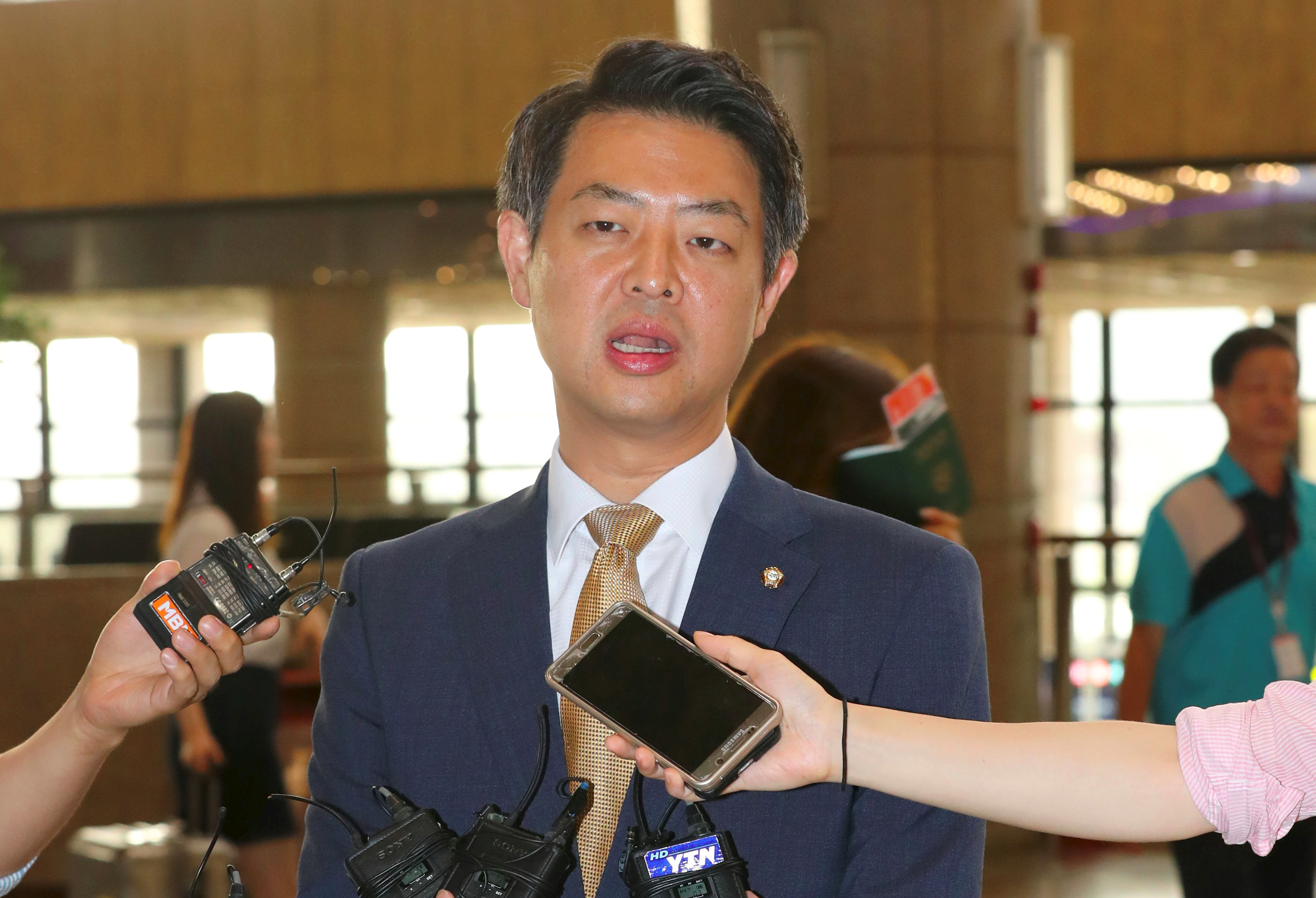 Kim Young-Ho, a lawmaker from South Korea's main opposition Minjoo Party, speaks to the media before departing for China at Gimpo airport in Seoul on August 8, 2016. South Korean opposition lawmakers defied President Park Geun-Hye and left for China on August 8 to discuss the deployment of a US anti-missile system that has opened a damaging rift between Seoul and Beijing. / AFP PHOTO / YONHAP / YONHAP / REPUBLIC OF KOREA OUT  NO ARCHIVES  RESTRICTED TO SUBSCRIPTION USE