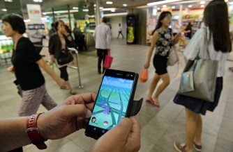 A man shows the Pokemon Go game on his smartphone while hunting outside a SMRT train station in Singapore on August 11, 2016. Pokemon Go was available in nine countries on August 6, including Singapore. / AFP PHOTO / ROSLAN RAHMAN