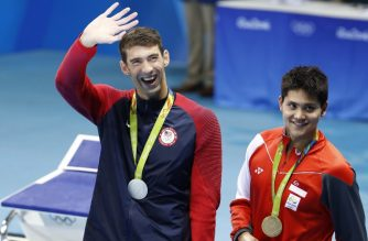 Silver medallist USA's Michael Phelps (L) waves nex to gold medallist Singapore's Schooling Joseph during the medal ceremony of the Men's 100m Butterfly Final during the swimming event at the Rio 2016 Olympic Games at the Olympic Aquatics Stadium in Rio de Janeiro on August 12, 2016.   / AFP PHOTO / Odd Andersen