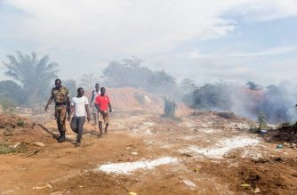 A policeman and members of the public leave the scene of an explosion at a garbage dump that left two people dead in Cotonou on September 9, 2016.  At least two people were killed scores more injured after an explosion at a garbage dump in Benin, police told AFP on September 9. The blast happened on the evening of September 8, with the fire erupting in Tori Avame, 40 kilometres (25 miles) from Benin's commercial hub, Cotonou.   / AFP PHOTO / YANICK FOLLY