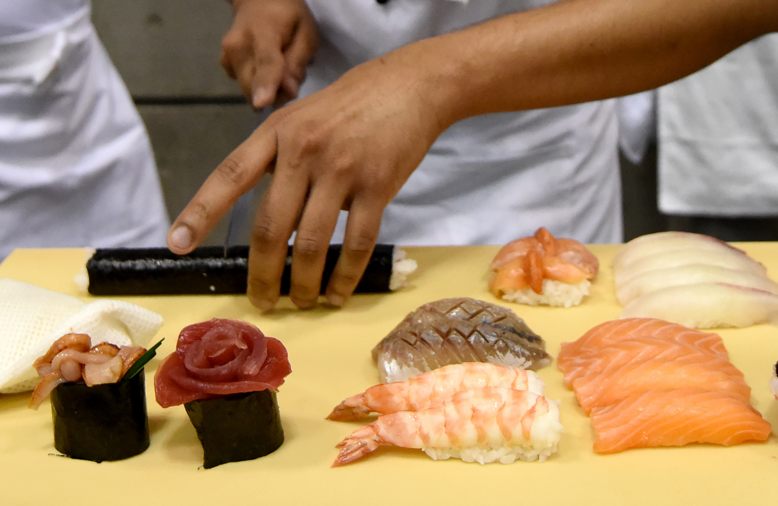 A young foreign sushi chef makes sushi at the World Sushi Cup Japan 2016 in Tokyo on August 18, 2016.  Twenty-seven sushi chefs from fourteen countries and two regions took part in the two-day competition in hygienic and technical skill of sushi making organized by Japan's Agriculture, Forestry and Fisheries Ministry. / AFP PHOTO / TORU YAMANAKA