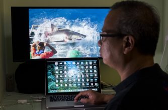 This picture taken on October 18, 2016 shows Chan Ming, who survived a close encounter with a great white shark while cage diving off Guadalupe Island, Mexico, watching the viral video of the great white shark on his computer in Shanghai.  Chan, who also teaches diving part time, escaped unhurt and according to him he returned to the water the following day.  / AFP PHOTO / JOHANNES EISELE