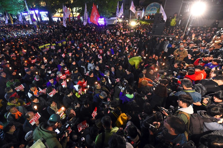Thousands of protesters hold a candle-lit rally in central Seoul on October 29, 2016, denouncing South Korean President Park Geun-Hye over a high-profile corruption and influence-peddling scandal involving her close friend. South Korean prosecutors on October 29 raided the homes and offices of senior advisers to President Park Geun-Hye, as she struggled with a corruption and influence-peddling scandal involving a close family friend. / AFP PHOTO / JUNG YEON-JE