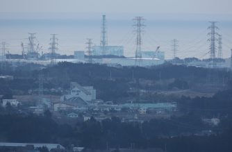 A general view shows the troubled Fukushima Daiichi nuclear power plant (rear) seen from Tomioka town in Fukushima prefecture on March 11, 2016, as people gather to remember the victims of the massive earthquake and tsunami disaster which hit northeastern Japan in 2011. Japan is marking on March 11 the fifth anniversary of the 2011 quake and tsunami that claimed some 18,500 lives, flattened coastal communities and set off the worst atomic crisis in a generation. / AFP PHOTO / JIJI PRESS / JIJI PRESS / Japan OUT